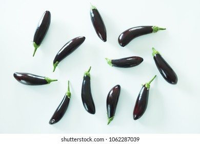 Bunch of ripe organic polished eggplants laid in composition on white background. Harvest heap of aubergine vegetables at table counter. Clean eating concept. Background, close up, flat lay, top view.