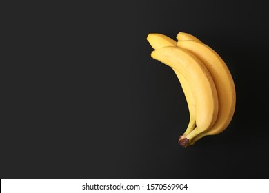 A bunch of ripe yellow bananas on a black background top view. Vegan fruit on a dark background copy space. Diet.