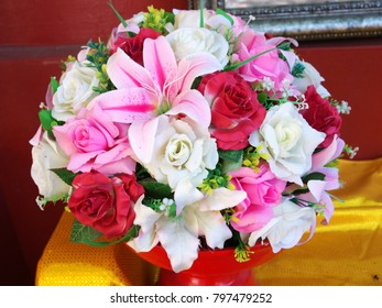 Bunch of rose and lily flowers in the red wooden tray.