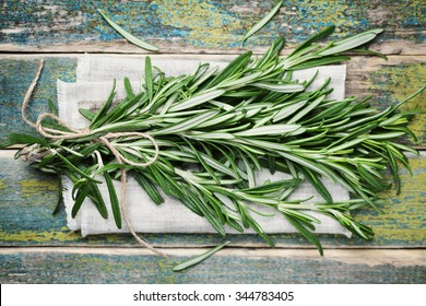 Bunch of rosemary on wooden table, rustic style, fresh organic herbs, top view