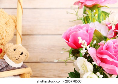 Bunch of roses and a teddy bear on wood