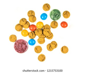 Bunch of scattered pepernoten cookies and chocolate money from above on white background for annual Sinterklaas holiday event in the Netherlands on december 5th