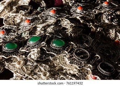 Bunch of silver bracelets with red and green gemstones with harsh shadows