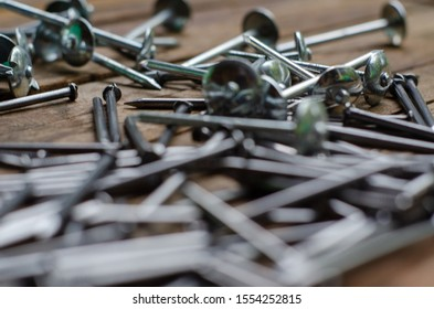 A bunch of silver nails over the wooden background