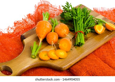 Bunch of small, round carrots (Parisian Heirloom Carrots) on wooden background. Studio Photo