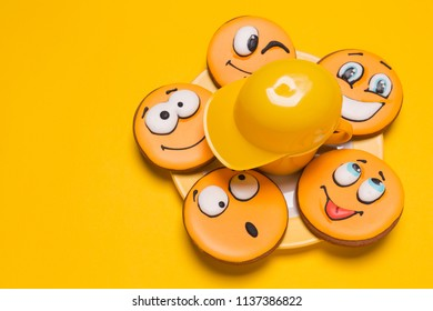 a bunch of smile cookies on a plate on a yellow background, beside a decorative baseball cap, children's gingerbread with different emotions, the concept