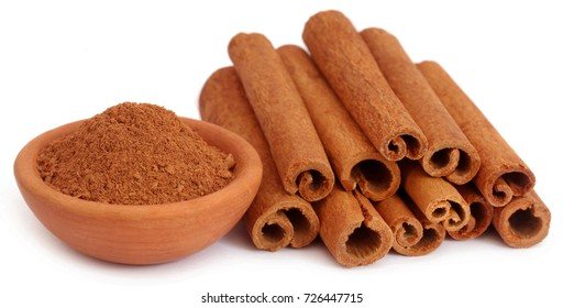 Bunch of some fresh aromatic cinnamon with powder spice in a pottery over white background