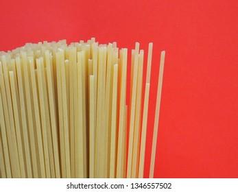 Bunch of spaghetti on orange background. Macro photography.