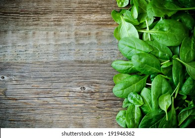 a bunch spinach leaves on a dark wood background. toning.