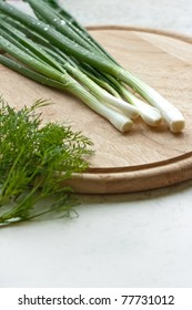 bunch of spring onions and dills on table