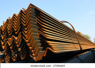 Bunch of steel angles in warehouse against a blue sky