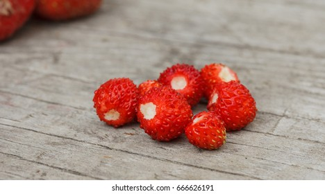 Bunch of strawberries and wild berries on wooden and grass natural background, dirty raw organic dessert