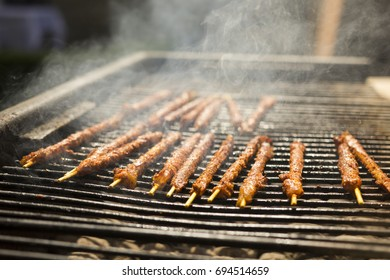 A bunch of tasty chicken rolls on brochettes (grilled meat on a wooden stick) on the barbecue. The meat and charcoals are releasing smoke. The grill is charred and greasy. The focus is on the rolls.