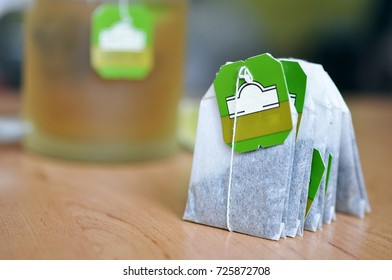 Bunch of tea bags of green tea with a cup of tea in the background