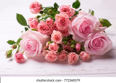 Bunch of tender pink roses flowers  on  white wooden background. Floral still life.  Selective focus.