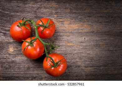 Bunch of tomatoes on the wooden table in natural light