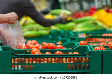 Bunch of tomatoes in plastic boxes in supermarket