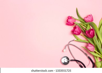 Bunch of tulips and stethoscope on pink background. Top view wiyh copy space. National Doctor's day. Happy nurse day.
