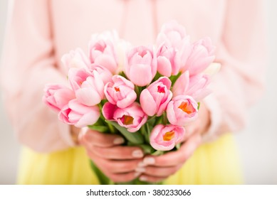 Bunch of tulips in woman's hands, shallow dof.