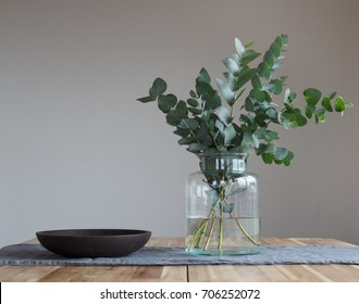 A bunch of twigs and green eucalyptus in a glass jar on the wooden table.