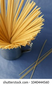 Bunch of uncooked Italian pasta spaghetti in a metal mug on a purple background. Macro shot, selective focus