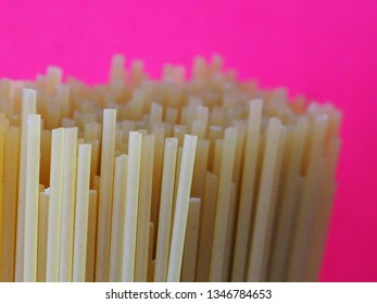 Bunch of uncooked spaghetti against a bright pink background. Selective focus. Macro photography.
