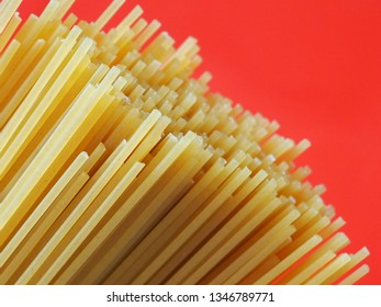 A bunch of uncooked spaghetti against orange background.