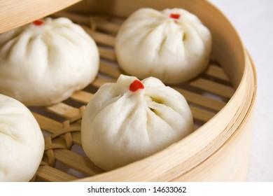 Bunch of vegetarian stuffed dumplings on a bamboo steamer. Main focus on the dumpling at the front.