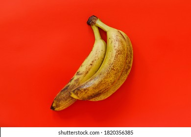 A bunch of very ripe organic bananas on red background top view