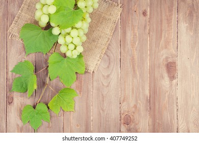 Bunch of white grapes with leaves on wooden background with copy space