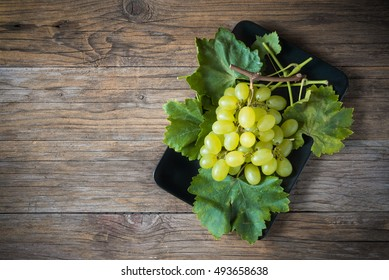 bunch of white grapes with leaves on wooden table