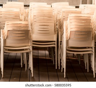 a bunch of white plastic chairs on wooden floor
