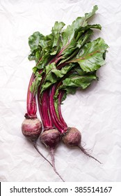 bunch of whole beetroots with green leaves, fresh from farmer's market, isolated on a paper background, top view