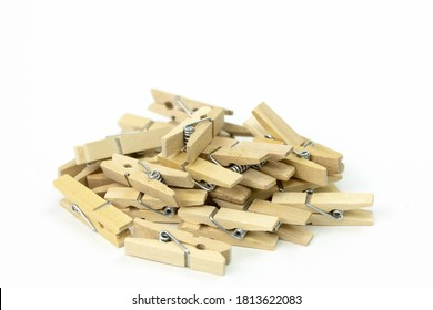 "bunch of wooden clothespins piled up in mess on white background close up . beech wood, natural materials ""no plastic!"" concept"