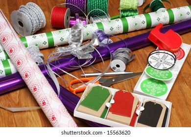 a bunch of wrapping paper, ribbons, label tags and other present wrapping material on an oak table