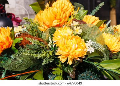 Bunch of yellow artificial flowers lying on a grave