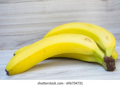 bunch of yellow bananas lie on a wooden background