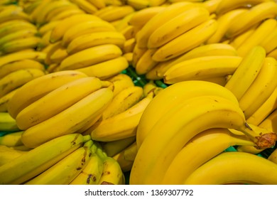 Bunch of yellow bananas on black background. Fresh and healthy.  Shallow depth of field, focus on the front banana.