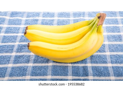 A bunch of yellow bananas on a blue towel