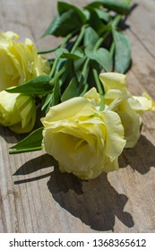 Bunch of yellow eustoma flowers (prairie gentian, lisianthus) on wooden background. Beautiful floral mockup. Space for your text. Top view, flat lay.