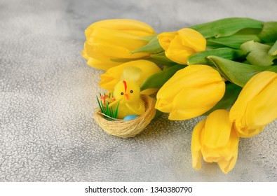 Bunch of yellow tulips and chicken-toy on a light background