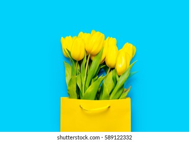 bunch of yellow tulips in cool shopping bag on the wonderful blue background