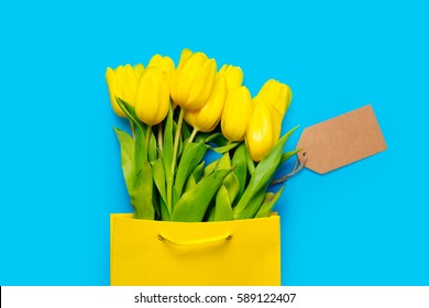 bunch of yellow tulips in cool shopping bag and price tag on the wonderful blue background