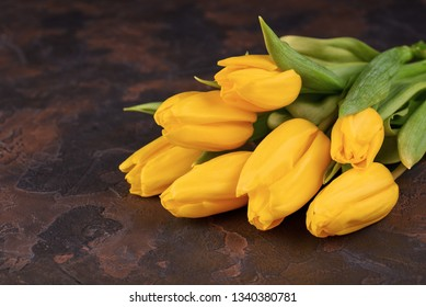 Bunch of yellow tulips on a dark background