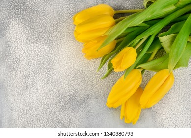 Bunch of yellow tulips on a light background