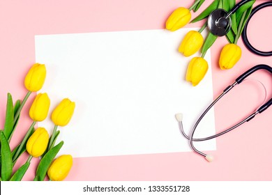 Bunch of yellow tulips and stethoscope on pink background. National Doctor's day. Happy nurse day. Top view wiyh copy space.