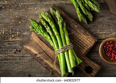 bunches of fresh green asparagus on wooden background, top view