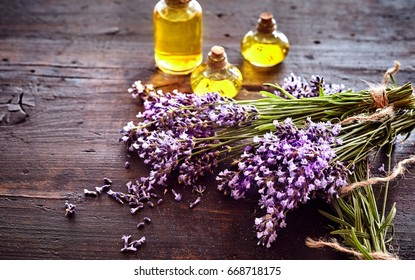 Bunches of fresh lavender with three small bottles of essential oil or extract for aromatherapy or alternative medicine lying on rustic wood with copy space