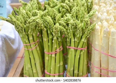 Bunches of fresh organic green and white asparagus with selective focus. Spring seasonal vegetables. Sprouts of delicious vegetarian green and white asparagus. Delicatessen spring asparagus