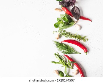 Bunches of fresh raw herbs - mint, thyme, dill, parsley, basil and tarragon, garlic and red pepper on a textured background. Top view. Copy space